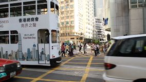 Traffic and pedestrians on street in Hong Kong. Public transport and pedestrians in central street of big asian city in rush hour. Passing by traffic and crowd stock video