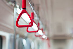 Public Transportation. Horizontal photo of red bus handles on blurry background. The handles are perfectly aligned. The background is very soft and the scene stock photo