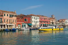 Public transportation boat passes by the Grand canal in Murano, Italy. Stock Photos