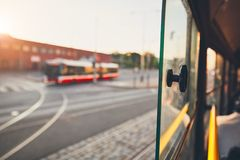 Public transportation in the city. Bus of the public transportation at the sunset. Selective focus on the window of the tram Stock Photos