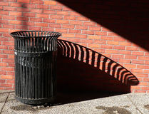 Public Trash Can casts a shadows. Black metal trashcan casts a long shadow, against red brick wall Royalty Free Stock Photography