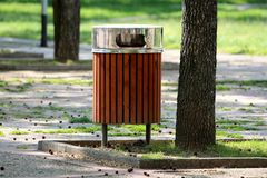 Public trash can made of narrow wooden boards with shiny metal top cover next to old tall tree surrounded with stone tiles in. Local park on warm sunny spring stock photos