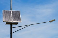 Public city light with solar panel powered on blue sky with clouds. Public urban light with a solar panel working on a blue sky with clouds. alternative energy Royalty Free Stock Photography