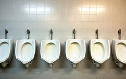 Public Urinals. A row of urinals in tiled wall in a public restroom Royalty Free Stock Images