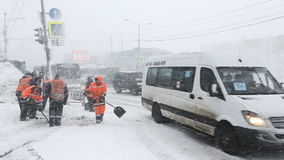 Public utility workers clean sidewalks of snow and ice near road with moving cars. PETROPAVLOVSK-KAMCHATSKY CITY, KAMCHATKA PENINSULA, RUSSIA - JAN 12, 2017 stock video