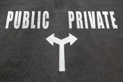 Public vs private choice concept. Two direction arrows on asphalt Stock Photos
