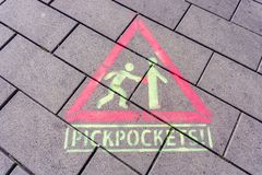 Public warning sign on pavement advising to beware Pickpoctkets. Public warning sign on pavement in Berlin Germany advising awareness of pickpockets Royalty Free Stock Photography