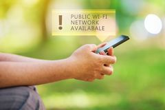 Public wi-fi network available. Message on smartphone in female hands, wireless internet hotspot in park Stock Images