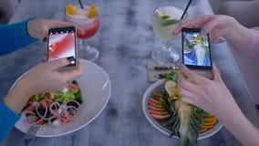 Publicando em blogs, as amigas modernas usam tecnologias móveis espertas e imagens da tomada da refeição apetitosa para redes soc video estoque