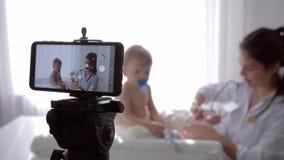 Publicando em blogs, a mulher do pediatra com estetoscópio examina profissionalmente pouco menino paciente durante a gravação do  vídeos de arquivo