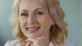 Publicidad de los cosméticos de la anti-edad Mujer madura atractiva que sonríe en cámara almacen de metraje de vídeo