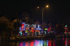 Publicidad de neón china colorida con reflexiones en el camino mojado Imagen de archivo libre de regalías