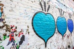 Publicidad rasguñada en la pared de la calle como fondo Imagenes de archivo