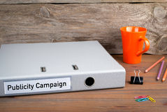 Publicity Campaign. Folder, Coffee Mug, colored pencils on wooden office desk Royalty Free Stock Photos