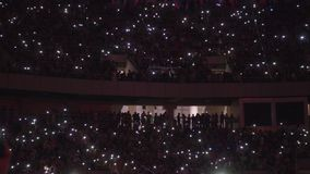 Publiek binnen een arena met de hun cellphoneschermen  stock videobeelden