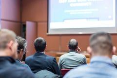 Publiek in conferentiezaal die aan presentatie op handelsconferentie luisteren stock foto