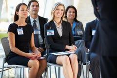 Publiek die aan Presentatie op Conferentie luisteren Stock Afbeeldingen