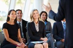 Publiek die aan Presentatie op Conferentie luisteren Stock Foto