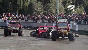Publiek die op twee monstervrachtwagens bij arena, extreme sporten letten stock footage