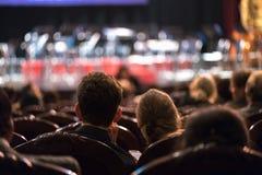 Publiek het letten op het overleg toont in het theater stock fotografie