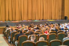 Publiek in Theater gesloten stadiumgordijn in een theater onscherp stock afbeelding