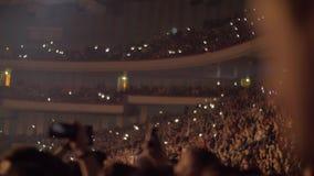 Publieks golvende handen en mobiele flitslichten bij het overleg stock footage