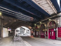 Pubs in Crutched Friars Street under the bridge of London Fenchurch station in London, England. LONDON, UNITED KINGDOM - March 19, 2017: Pubs in Crutched Friars Stock Photo