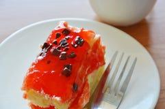 Puce de chocolat d'écrimage de gâteau de beurre de fraise avec la tasse de fourchette et de café image stock