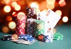 Puces de casino et cartes, deux as sur la table verte jouante contre les lumières lumineuses de bokeh Contexte de thème de jeu de Photographie stock