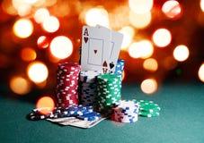 Puces de casino et cartes, deux as sur la table verte jouante contre les lumières lumineuses de bokeh Contexte de thème de jeu de Image stock