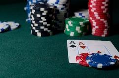 Puces de casino et paires d'as sur la table verte Jeu de tisonnier Photographie stock libre de droits