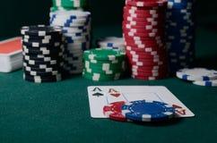 Puces de casino et paires d'as sur la table verte Jeu de tisonnier Photographie stock