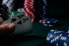 Puces de casino et paires d'as sur la table verte Jeu de tisonnier Image libre de droits