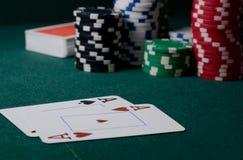 Puces de casino et paires d'as sur la table verte Jeu de tisonnier Images libres de droits