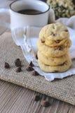 Puces de chocolat de biscuits avec du café et le conseil noir sur le jute, petit déjeuner, matin frais Photos stock