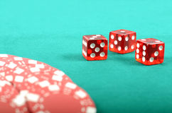 Puces de jeu de tisonnier sur une table de jeu verte Image stock