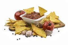 Puces de tortilla avec l'immersion chaude, l'ail et les tomates Images stock