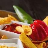 Puces de tortilla d'un plat bleu avec le Salsa épicé de tomate mexicain Image stock