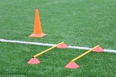 Puces et cône pour la formation du football Folâtre le fond avec des inscriptions sur une pelouse artificielle Images stock