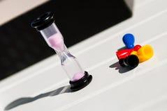 Puces et sablier colorés sur une table en bois blanche Photo stock