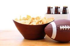Puces, football et paquet de six de bière Photos stock