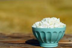 Puchar domowej roboty chałupa ser na drewnianym wieśniaka stole na złocistym pszenicznego pola tle zdjęcie stock