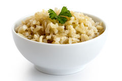 Puchar gotujący dłudzy zbożowi brown ryż z zieloną pietruszką odizolowywającą zdjęcia royalty free