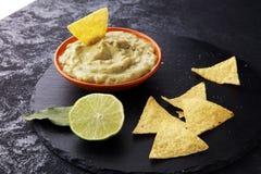 Puchar guacamole z tortilla układami scalonymi na ciemnym tle Fotografia Stock