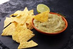 Puchar guacamole z tortilla układami scalonymi na ciemnym tle Zdjęcia Stock