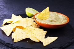 Puchar guacamole z tortilla układami scalonymi na ciemnym tle Fotografia Royalty Free