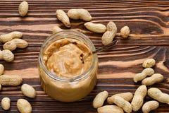 Puchar masło orzechowe i arachidy na drewnianym tle od obrazy stock
