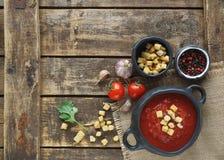 Puchar pomidorowa polewka z goździkowym i czarnym pieprzem na nieociosanym drewnianym tle, odgórny widok Obraz Stock
