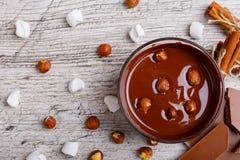 Puchar rozciekła dojna czekolada z hazelnuts na drewnianym stołowym zakończeniu Obrazy Stock
