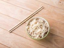Puchar ryż z drewnianymi chopsticks na stole. Obrazy Royalty Free